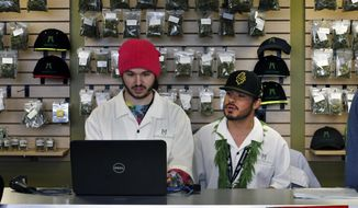 In this Jan. 1, 2014, file photo, employees  Chris Broussard, left, and David Marlow, work behind sales counter inside Medicine Man marijuana retail store, which opened as a legal recreational retail outlet in Denver. Colorado made roughly $2 million in marijuana taxes in January, state revenue officials reported Monday, March 10, 2014, in the world's first accounting of the recreational pot business. (AP Photo/Brennan Linsley, File)