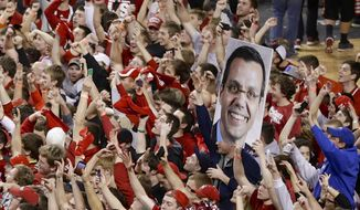 Celebrating Nebraska fans carry a sign of Nebraska coach Tim Miles as they fill the court following an NCAA college basketball game in Lincoln, Neb., Sunday, March 9, 2014. Nebraska won 77-68. (AP Photo/Nati Harnik)
