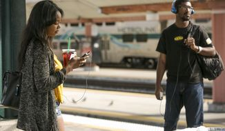 High school senior, Kaylen Gordon, 18, left, waits for a Metro Rail light train on the Gold Line at Union Station in Los Angeles Monday, March 10, 2014. Americans are boarding public buses, trains and subways in greater numbers than any time in half a century. Nearly 10.7 billion trips in 2013, to be precise, the highest total since 1956, according to ridership data reported by transit systems nationally and released Monday by the American Public Transportation Association. (AP Photo/Damian Dovarganes)