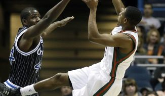 Milwaukee Bucks' Brandon Knight, right, puts up a shot against Orlando Magic's Andrew Nicholson during the first half of an NBA basketball game, Monday, March 10, 2014, in Milwaukee. (AP Photo/Jeffrey Phelps)