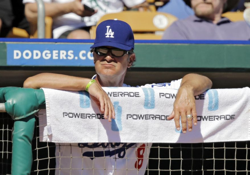 Los Angeles Dodgers manager Don Mattingly  watches from the dugout in the fifth inning of a spring exhibition baseball game against the Oakland Athletic,s Monday, March 10, 2014, in Glendale, Ariz. (AP Photo/Mark Duncan)