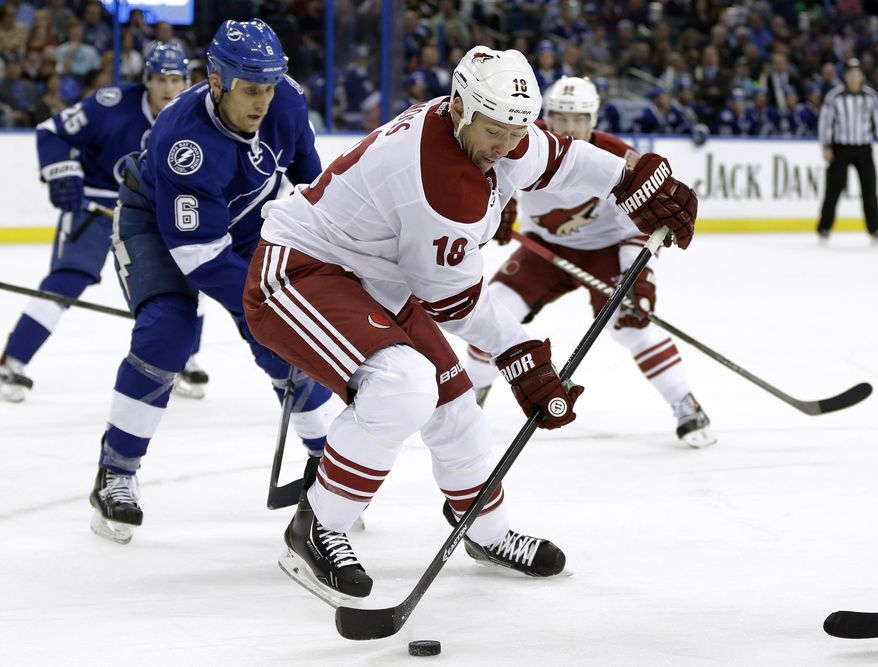 Phoenix Coyotes right wing David Moss (18) controls the puck in front of Tampa Bay Lightning defenseman Sami Salo (6), of Finland, during the first period of an NHL hockey game, Monday, March 10, 2014, in Tampa, Fla. (AP Photo/Chris O'Meara)