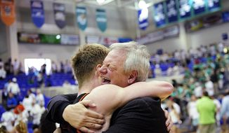 An emotional Mercer Men's Basketball Head Coach Bob Hoffman, right, hugs player Jakob Gollon after their win Sunday, March 9, 2014 at Alico Arena in Estero, Fla. The two faced off in the Atlantic Sun Men's Basketball Tournament championship. The Bears held off the Eagles 68-60 and earn an automatic bid to the NCAA tournament. (AP Photo/Naples Daily News, Corey Perrine)