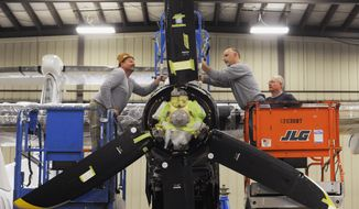 In this Oct. 21, 2013 photo, Jerry Hampton, left, grabs a wrench from Brian Ward while doing maintenance at Emery Air Inc., in Rockford, Ill., on the engine of a plane brought in from Columbia, Ill. Emery is one of the almost 100 aerospace and aviation companies in Rockford. (AP Photo/Rockford Register Star, Brent Lewis)  MANDATORY CREDIT