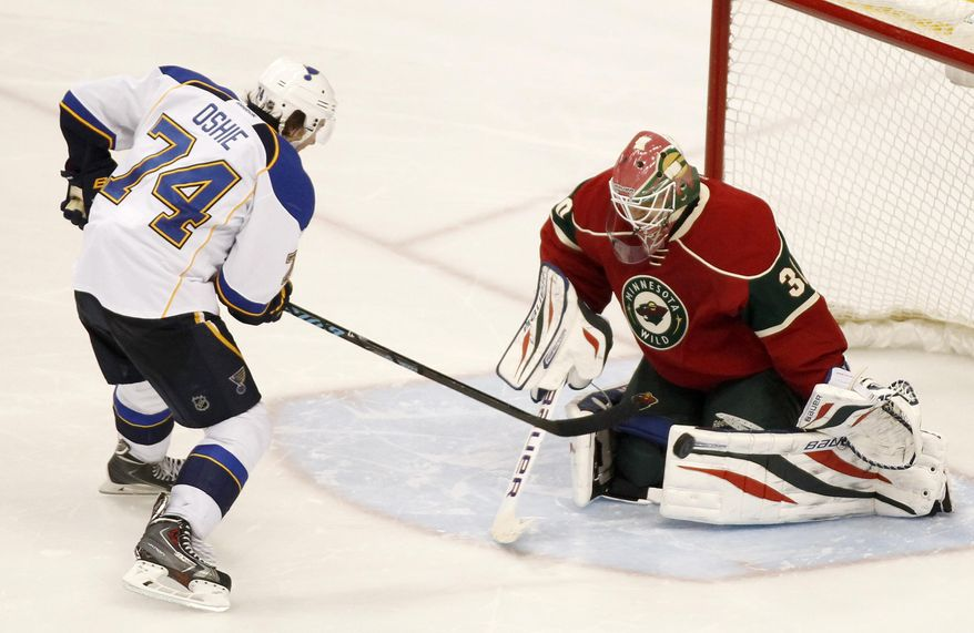 St. Louis Blues right wing T.J. Oshie (74) scores on Minnesota Wild goalie Ilya Bryzgalov (30) in the shoot out during their NHL hockey game Sunday, March 9, 2014 in St. Paul, Minn.. The Blues defeated the Wild 3-2 in a shootout.(AP Photo/Andy Clayton-King)