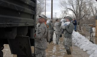 CORRECTS YEAR TO 2014 This March 9, 2014 photo provided by the Wyoming National Guard shows Guard members, with the 153rd Airlift Wing and the 920th Forward Support Company, civilian volunteers and town employees forming a chain to deliver sandbags to flooding houses in Graybull, Wyo. (AP Photo/Wyoming National Guard)