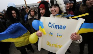 "Crimean Tatars shout slogans during the pro-Ukraine rally in Simferopol, Crimea, Ukraine, Monday, March 10, 2014.  Russian President Vladimir Putin on Sunday defended the separatist drive in the disputed Crimean Peninsula as in keeping with international law, but Ukraine's prime minister vowed not to relinquish ""a single centimeter"" of his country's territory. The local parliament in Crimea has scheduled a referendum for next Sunday. (AP Photo/Darko Vojinovic)"