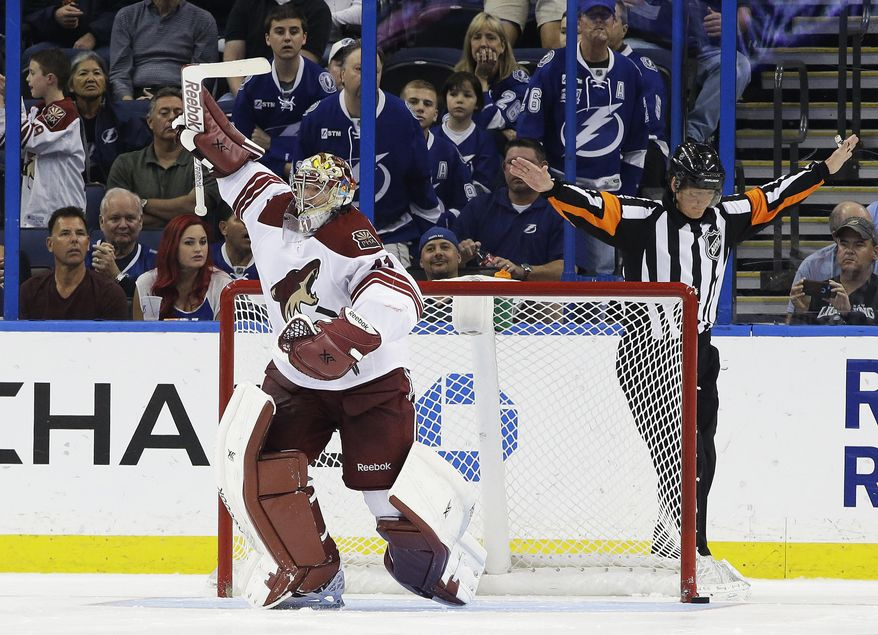 Phoenix Coyotes goalie Mike Smith (41) celebrates after stopping Tampa Bay Lightning right wing Ryan Callahan (24) during a shoot out in an NHL hockey game Monday, March 10, 2014, in Tampa, Fla. The Coyotes won the game 4-3. Making the call is referee Rob Martell. (AP Photo/Chris O'Meara)