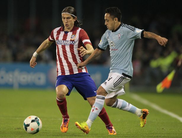Atletico's Filipe Luis from Brasil, left, in action with Celta's Fabian Orellana from Chile during a Spanish La Liga soccer match at the Balaidos stadium in Vigo, Spain, Saturday, March 8, 2014. (AP Photo/Lalo R. Villar)