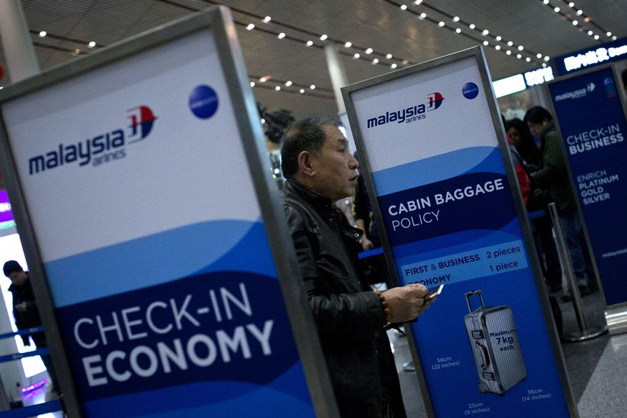 A passenger holds his passport and boarding pass after he checked in his luggage at a Malaysia Airlines check-in counter at Capital International Airport in Beijing, Monday, March 10, 2014.  Almost three days after the plane with 239 people on board vanished en route from Kuala Lumpur to Beijing, no debris has been spotted in Southeast Asian waters, hampering efforts to begin the investigation into how the plane disappeared. (AP Photo/Alexander F. Yuan)