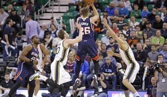 Atlanta Hawks' Kyle Korver (26) shoots as Utah Jazz's Gordon Hayward (20) and Enes Kanter, right, defend in the first quarter during an NBA basketball game Monday, March 10, 2014, in Salt Lake City. (AP Photo/Rick Bowmer)