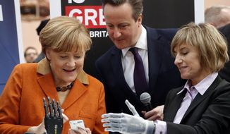 Claudia Breidbach, right, demonstrates a  bionic hand that is steerable by a mobile phone to German Chancellor Angela Merkel and British Prime Minister David Cameron, center,  during the opening day of the computer fair CeBIT in Hannover, Germany, Monday, March 10, 2014. Great Britain is the partner country at this year's CeBIT which runs through March 14.(AP Photo/Frank Augstein)