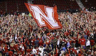 Nebraska fans storm the court following a 77-68 win over Wisconsin in an NCAA college basketball game in Lincoln, Neb., Sunday, March 9, 2014. (AP Photo/Nati Harnik)