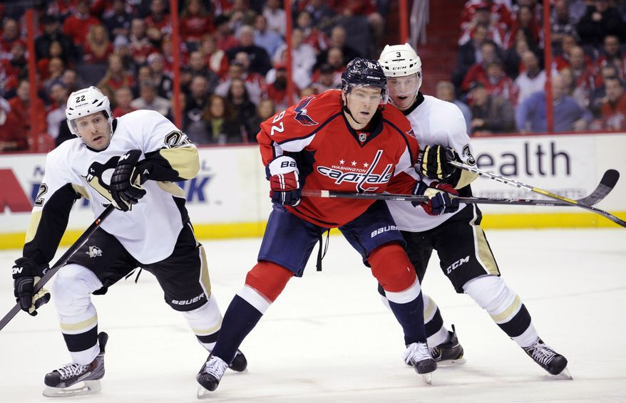 Washington Capitals center Evgeny Kuznetsov (92), of Russia, fights for position against Pittsburgh Penguins defenseman Olli Maatta (3), of Finland, and Lee Stempniak (22) during the first period of an NHL hockey game, Monday, March 10, 2014, in Washington. (AP Photo/Nick Wass)