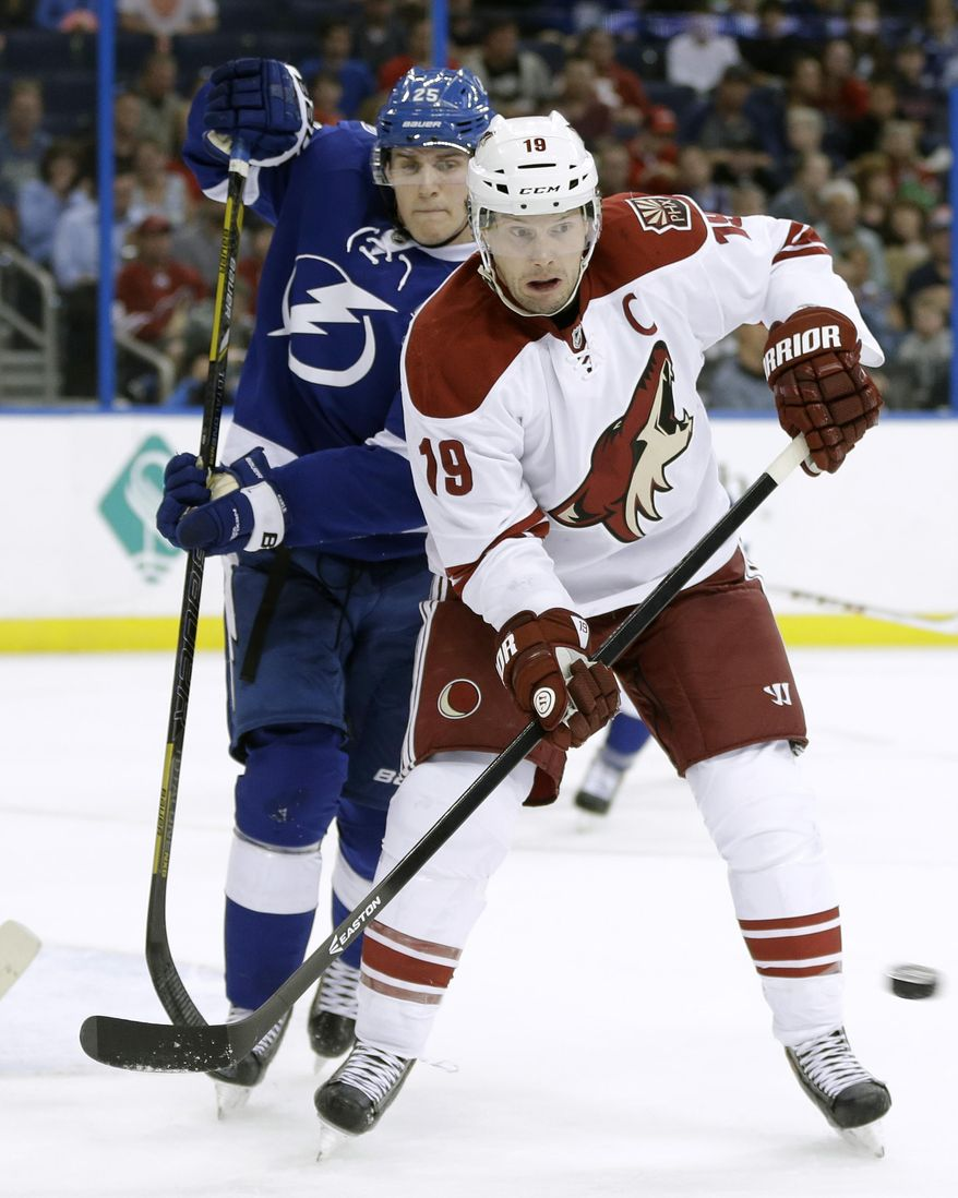 Phoenix Coyotes right wing Shane Doan (19) looks to deflect the puck as he stands in front of Tampa Bay Lightning defenseman Matt Carle (25) during the first period of an NHL hockey game, Monday, March 10, 2014, in Tampa, Fla. (AP Photo/Chris O'Meara)
