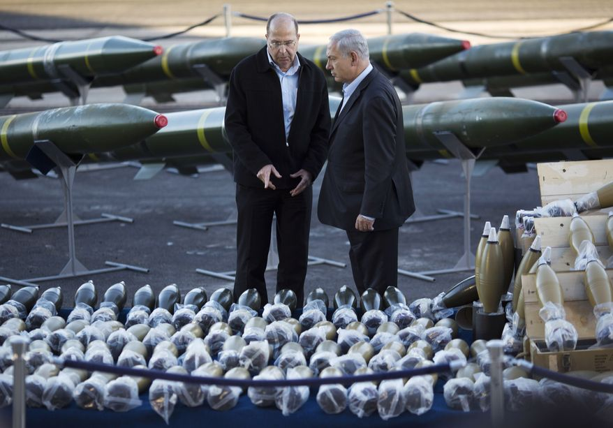 Israel's Prime Minister Benjamin Netanyahu, right, and Israel's Defense Minister Moshe Yaalon, left, examine dozens of mortar shells and rockets on display after being seized from the Panama-flagged KLOS C civilian cargo ship that Israel intercepted last Wednesday off the coast of Sudan, at a military port in the Red Sea city of Eilat, southern Israel, Monday, March 10, 2014. Israel has alleged the shipment was orchestrated by Iran and was intended for Islamic militants in Gaza, a claim denied by Iran and the rockets' purported recipients. Questions remain, including how the rockets would have been smuggled into Gaza, largely cut off from the world by a border blockade enforced by Israel and Egypt. (AP Photo/Ariel Schalit)