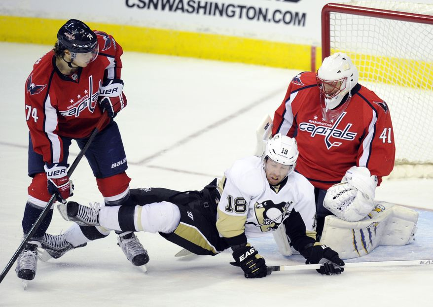 Pittsburgh Penguins left wing James Neal (18) gets tangles up with Washington Capitals defenseman John Carlson (74) as Capitals goalie Jaroslav Halak (41), of Slovakia, looks on during the third period of an NHL hockey game, Monday, March 10, 2014, in Washington. The Penguins won 3-2.(AP Photo/Nick Wass)