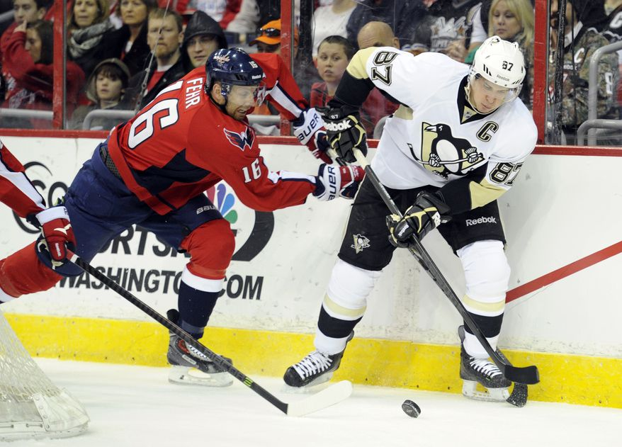 Washington Capitals right wing Eric Fehr (16) battles for the puck against Pittsburgh Penguins center Sidney Crosby (87) during the first period of an NHL hockey game, Monday, March 10, 2014, in Washington. (AP Photo/Nick Wass)