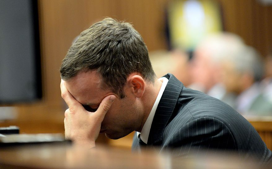 Oscar Pistorius buries his head in his hand as he listens to cross questioning, in the second week of his trial, about the events surrounding the shooting death of his girlfriend Reeva Steenkamp, in court during his trial in Pretoria, South Africa, Monday, March 10, 2014. Pistorius is charged with the shooting death of his girlfriend  Steenkamp, on Valentines Day in 2013. (AP Photo/Bongiwe Mchunu, Pool)