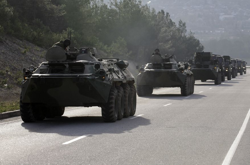 A convoy of military vehicles bearing no license plates travels on the road from Sevastopol to Simferopol, Crimea, Ukraine, Monday, March 10, 2014. Ukraine's foreign minister said Monday his country already feels like it's almost in a state of war after Russian forces took effective control of Ukraine's Crimean Peninsula. (AP Photo/Darko Vojinovic)