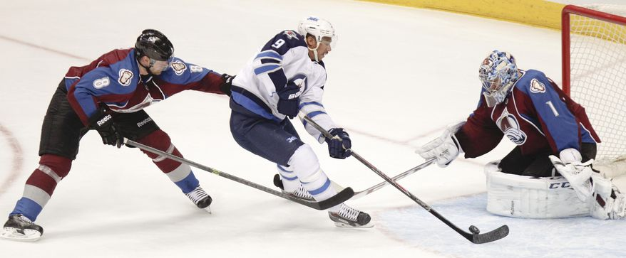 Winnipeg Jets' Evander Kane, center, gets by Colorado Avalanche's Jan Hejda, left,  for a shot on goal while Colorado Avalanche goalie Semyon Varlamov, right, makes the save during the first period of an NHL hockey game on Monday, March 10, 2014 in Denver. (AP Photo/Barry Gutierrez)