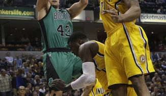 Boston Celtics center Kris Humphries (43) shoots over Indiana Pacers defenders David West (21) and Roy Hibbert during the first half of an NBA basketball game in Indianapolis, Tuesday, March 11, 2014. (AP Photo/AJ Mast)