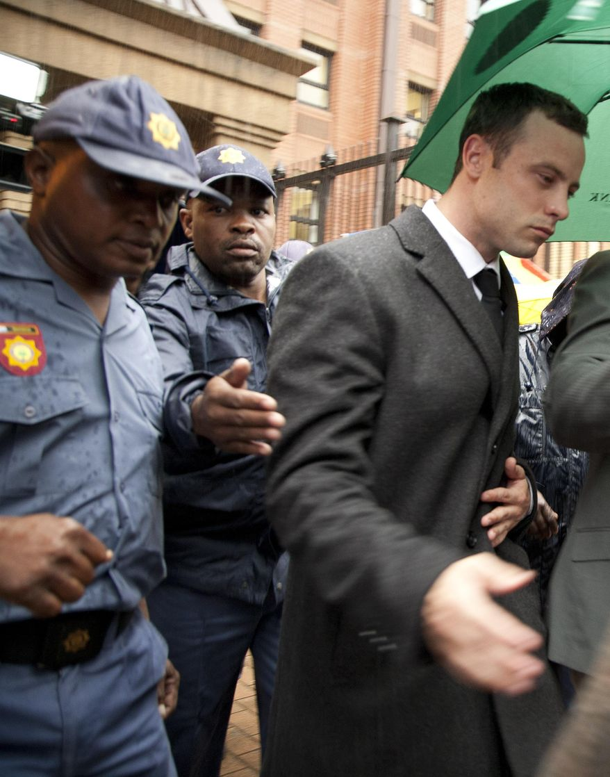 Oscar Pistorius, right,  is escorted by police officers as he leaves the high court in Pretoria, South Africa, Monday, March 10, 2014. Pistorius is charged with murder for the shooting death of his girlfriend, Reeva Steenkamp, on Valentines Day in 2013. (AP Photo/Themba Hadebe)