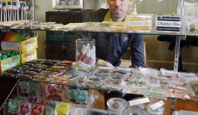 **FILE** Matt Brown, co-owner of Denver's new My 420 Tours, looks over a sampling of marijuana edibles at a dispensary in Denver. He has sold 160 tour packages to visiting pot smokers for the April 20 weekend, the first 420 Day in Colorado and Washington since voters decided to make pot legal.