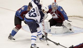 Winnipeg Jets' Dustin Byfuglien (33) makes a shot on goal, Colorado Avalanche goalie Semyon Varlamov (1), of Russia, makes the save during the first period of an NHL hockey game on Monday, March 10, 2014 in Denver. (AP Photo/Barry Gutierrez)