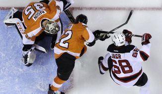 New Jersey Devils' Jaromir Jagr (68), of the Czech Republic, scores a goal past Philadelphia Flyers' Mark Streit (32), of Switzerland, and Steve Mason (35) during the third period of an NHL hockey game, Tuesday, March 11, 2014, in Philadelphia. New Jersey won 2-1. (AP Photo/Matt Slocum)