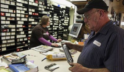 In this Feb. 13, 2014 photo, Clyde Lambdin checks out newly received parts for a restoration project while sitting at the front desk with his wife, Shirley, at Lambdin Mower Repair in Sullivan, Ill. (AP Photo/Herald & Review, Jim Bowling)