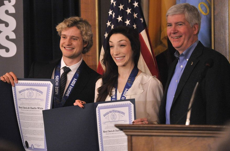 Michigan Gov. Rick Snyder right, smiles after presenting Michigan's olympic gold medal figure skaters, Charlie White, left, and Meryl Davis with special recognitions as they are honored at the Capitol Tuesday morning, March 11, 2014, in Lansing, Mich. (AP Photo/Detroit News, Dale G. Young)  DETROIT FREE PRESS OUT, MAGS OUT, MANDATORY CREDIT