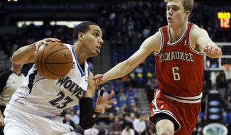 Minnesota Timberwolves' Kevin Martin, left, eyes the basket as Milwaukee Bucks' Nate Wolters defends in the first quarter of an NBA basketball game, Tuesday, March 11, 2014, in Minneapolis. (AP Photo/Jim Mone)