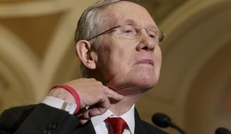 Senate Majority Leader Harry Reid of Nev. makes a cutting gesture across his neck, referencing House Oversight Committee Chairman Rep. Darrell Issa, R-Calif., who caused an uproar last week when he made the same gesture to order microphones cut as the top Democrat on his panel was trying to speak about the Internal Revenue Service scandal over targeting of conservative political groups,  Tuesday, March 11, 2014, during a news conference on Capitol Hill in Washington, Tuesday, March 11, 2014. Reid said that he thought the accusations of IRS misdeeds deserved answers. (AP Photo/J. Scott Applewhite)