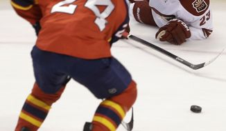 Florida Panthers right wing Brad Boyes (24) and Phoenix Coyotes defenseman Oliver Ekman-Larsson (23), of Sweden, battle for the puck during the second period of an NHL hockey game, Tuesday, March 11, 2014, in Sunrise, Fla. (AP Photo/Wilfredo Lee)