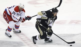 Pittsburgh Penguins' Sidney Crosby (87) brings the puck up the ice past Washington Capitals' Jason Chimera (25) during the first period of an NHL hockey game, Tuesday, March 11, 2014 in Pittsburgh. (AP Photo/Keith Srakocic)