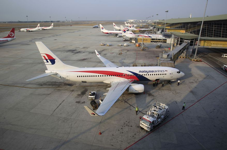 Ground staff work on a Malaysia Airlines plane at Kuala Lumpur International Airport in Sepang, Malaysia, Wednesday, March 12, 2014. The missing Malaysian jetliner may have attempted to turn back before it vanished from radar, but there is no evidence it reached the Strait of Malacca, Malaysia's air force chief said Wednesday, denying reported remarks he said otherwise. The statement suggested continued confusion over where the Boeing 777 might have ended up, more than four days after it disappeared en route to Beijing from Kuala Lumpur with 239 people on board. (AP Photo/Lai Seng Sin)