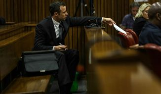 Oscar Pistorius hands a note to his defense team as he listens to cross questioning about the events surrounding the shooting death of his girlfriend Reeva Steenkamp, in court during his trial in Pretoria, South Africa, Tuesday, March 11, 2014. Pistorius is charged with the shooting death of Steenkamp, on Valentines Day in 2013. (AP Photo/Kevin Sutherland, Pool)