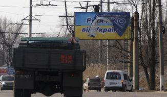 "Workers place an advertisement over a poster which reads, ""Hands off Ukraine"" in Perevalsk, eastern Ukraine, Tuesday, March 11, 2014. The Organization for Security and Cooperation in Europe (OSCE) is sending a new team to observe military developments in tense regions of Ukraine after pro-Russian forces rebuffed previous attempts to monitor Crimea. (AP Photo/Sergei Grits)"