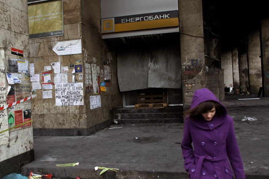 A woman walks past a local bank set on fire in Kiev's Independence Square, the epicenter of the country's unrest, in Ukraine on Feb. 25. The Obama administration is hoping the crisis in Ukraine will breathe new life into its stalled efforts to pass legislation reforming the International Monetary Fund in Congress this year. (associated press)
