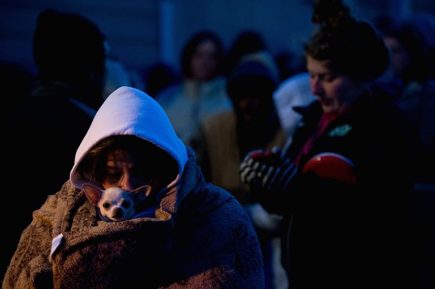 Bridget Morrill of Raphine, Va., and her dog Rox try to stay warm as she waits to see a doctor. The Remote Area Medical organization offers health care to people and their pets. For Obamacare, Virginia opted for using the federal marketplace. (Andrew Harnik/The Washington Times)