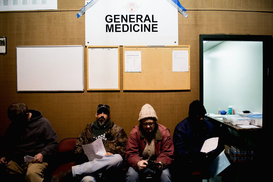 """WAITING: Patients at the Remote Area Medical clinic at Southern Virginia University are the kinds of people the Affordable Care Act is designed to help, but few have shopped for insurance. """"Nobody knows what it's about,"""" one person said. (Photographs by Andrew Harnik/The Washington Times)"""