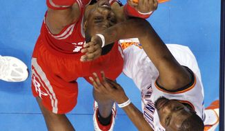 Houston Rockets center Dwight Howard, left, dunks in front of Oklahoma City Thunder forward Kevin Durant during the third quarter of an NBA basketball game in Oklahoma City, Tuesday, March 11, 2014. Oklahoma City won 106-98. (AP Photo/Sue Ogrocki)