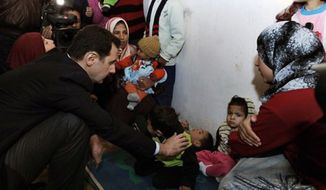 Syrian president Bashar Assad, center left, visits a shelter of internally displaced people in the Damascus suburb of Adra, Syria, Wednesday, March 12, 2014. (Associated Press)