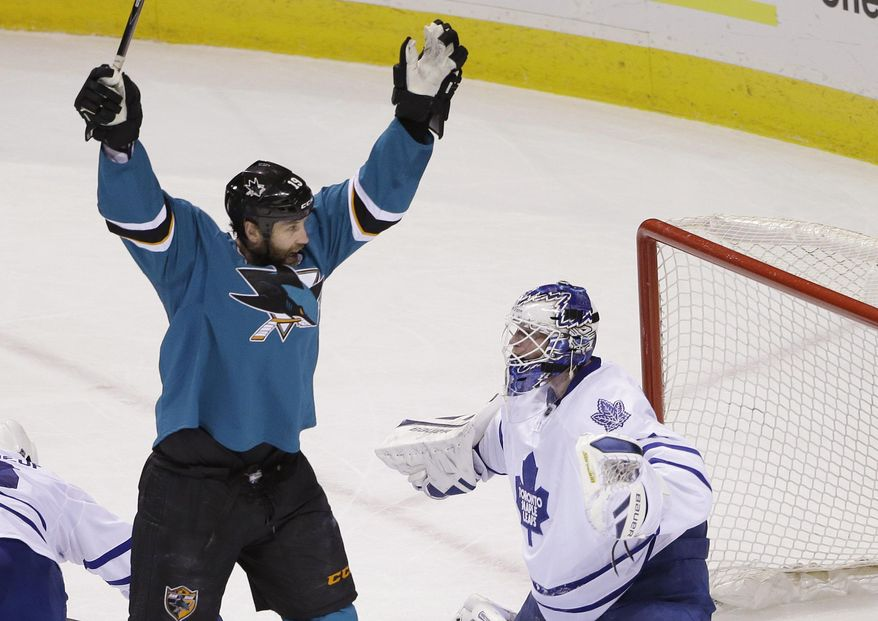 San Jose Sharks' Joe Thornton, left, celebrates a goal by teammate Brent Burns next to Toronto Maple Leafs goalie James Reimer during the first period of an NHL hockey game Tuesday, March 11, 2014, in San Jose, Calif. (AP Photo/Marcio Jose Sanchez)