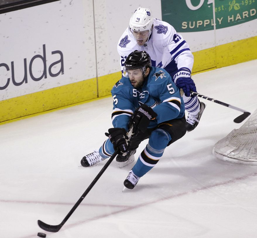 San Jose Sharks' Jason Demers (5) controls the puck in front of Toronto Maple Leafs' James van Riemsdyk during the first period of an NHL hockey game Tuesday, March 11, 2014, in San Jose, Calif. (AP Photo/Marcio Jose Sanchez)
