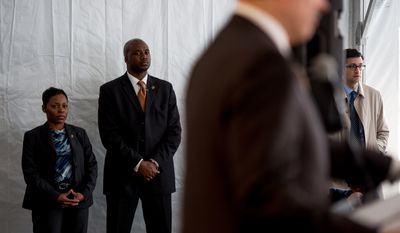 Security and aids listen to Washington, D.C. Mayor Vincent C. Gray, foreground, as he speaks to the media following a ceremonial groundbreaking on the long awaited Skyland Town Center at 2646 Naylor Road, SE in Ward 7, Washington, D.C., Wednesday, March 12, 2014. (Andrew Harnik/The Washington Times)