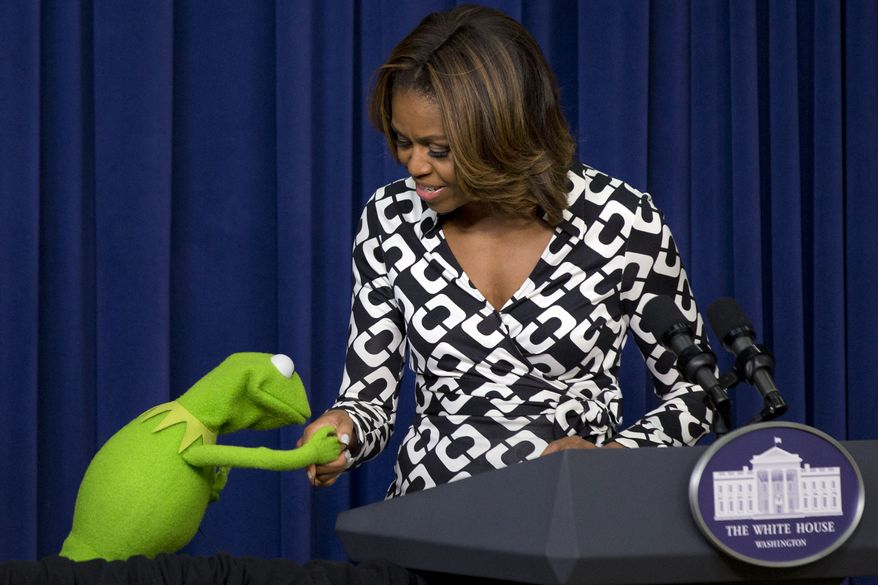 """Kermit the Frog kisses the hand of first lady Michelle Obama, during an event for children in military families in the South Court Auditorium of the Eisenhower Executive Office Building on the White House complex, Wednesday, March 12, 2014, before a screening of Disney's """"Muppets Most Wanted"""" movie as part of the Joining Forces initiative. (AP Photo/Jacquelyn Martin)"""