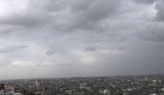 A trail of smoke from rockets fired by Palestinian militants from Gaza toward Israel is seen above Gaza City on Wednesday, March 12, 2014. The militant group Islamic Jihad in Gaza said it fired 20 rockets toward Israel on Wednesday, in retaliation for an Israeli airstrike that killed three of its members the day before. (AP Photo/Adel Hana)