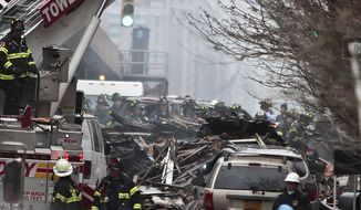 Firefighters continue to investigate and remove debris from an explosion in Harlem, Wednesday, March 12, 2014 in New York. A gas leak triggered an explosion that shattered windows a block away, rained debris onto elevated commuter railroad tracks close by, cast a plume of smoke over the skyline and sent people running into the streets. (AP Photo/Bebeto Matthews)